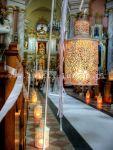 Aleja ślubna w kościele z białym dywanem i lampionami