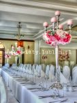Dekoracja kwiatowa sali weselnej wykonana na wysokich kandelabrach